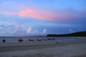 thai longboats under pink clouds